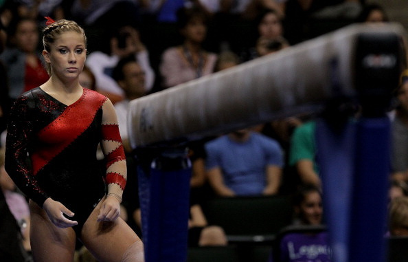 Shawn Johnson contemplates the beam